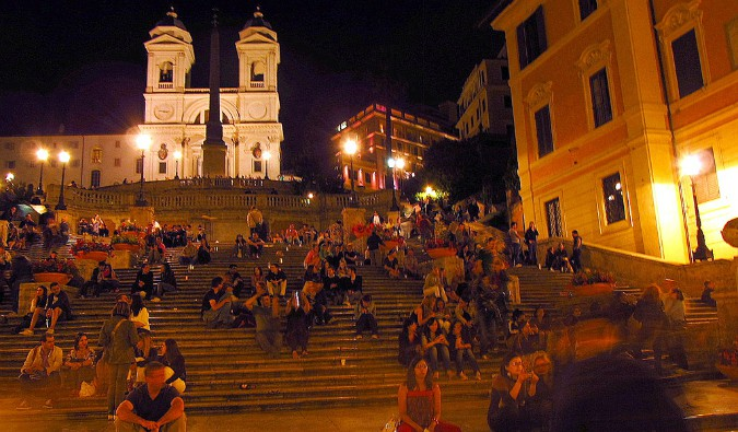 People sitting on stairs near the sidewalk bars in Rome