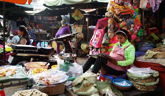 A local woman at a market stall reading a magazine while she works in Phnom Penh, Cambodia