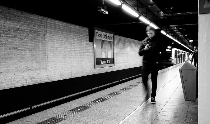 Man walking and using his smartphone in NYC subway tunnel