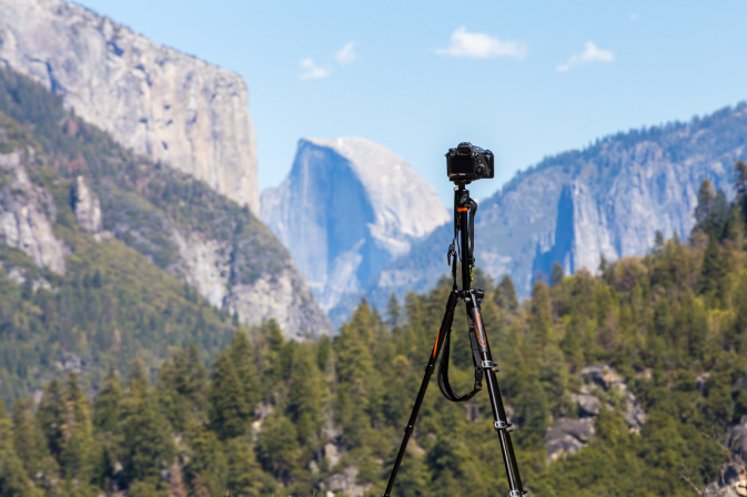 Camera and tripod set up in front of a mountain and nature