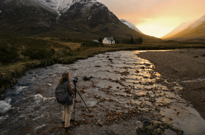 Photographer taking photo of a sun setting on a natural landscape