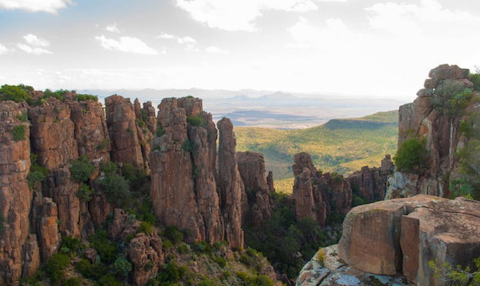 Tall rock formations in the hills of South Africa, leading to a sweeping valley