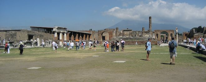 Tourists walking around the grounds of the Pompeii forum