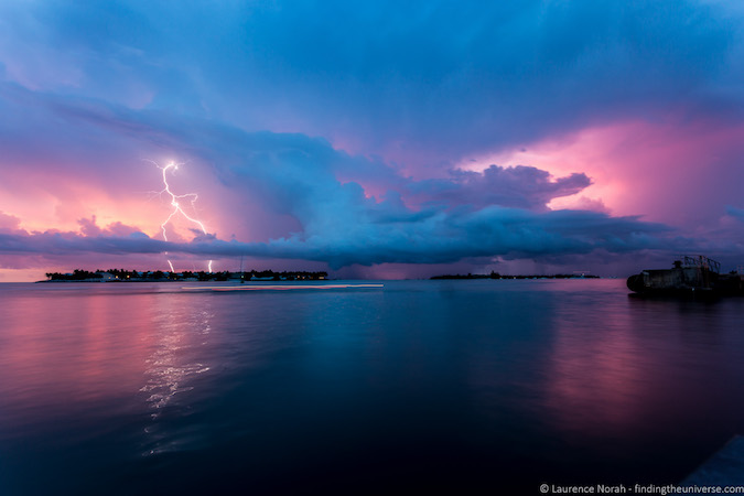 Blue dark pink nature photo of lightning at dusk