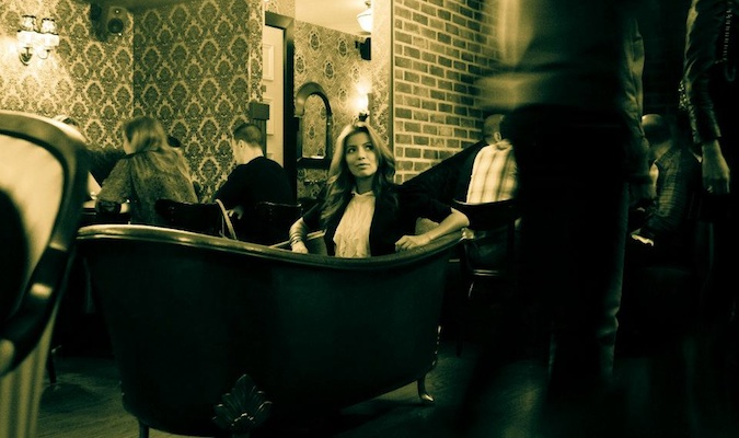 Girl sitting in a bathtub, a highlight of the popular NY speakeasy appropriately named Bathtub Gin