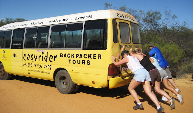 A broken down Oz Experience backpacker bus being pushed