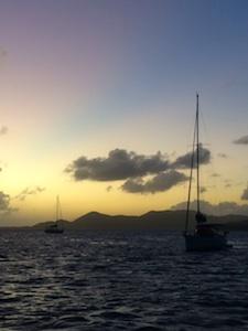 boats sailing the british virgin islands at sunset