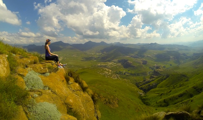 kristin from be my travel muse sitting on a mountain ledge in south africa thinking