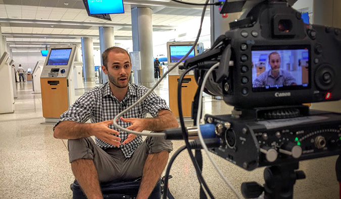Scott filming a television interview at an empty airport