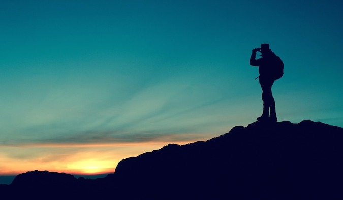 the silhouette of a backpacker standing on a cliff at sunset