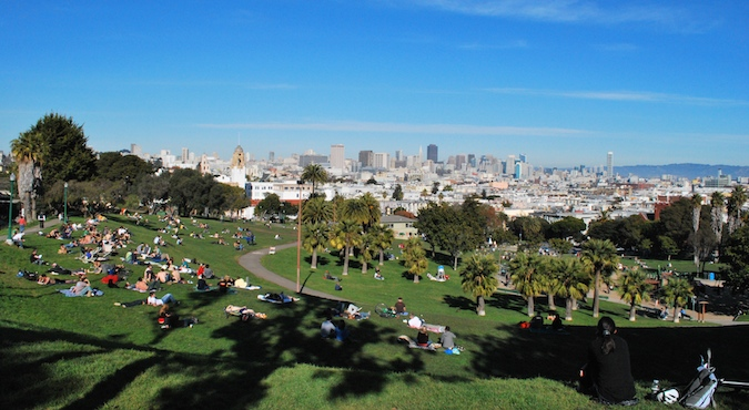 Groups of people hanging out on the lawn in the Mission District on a nice day in sunny San Francisco