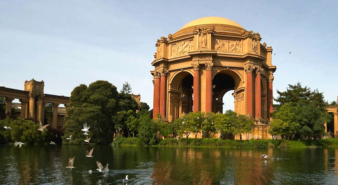 Gorgeous photo of dome surrounded by the water, shrubbery and birds at the Palace of Fine Arts taken during the golden hour