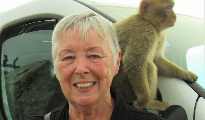 Senior traveler Sherrill with a monkey on her shoulder on a trip overseas