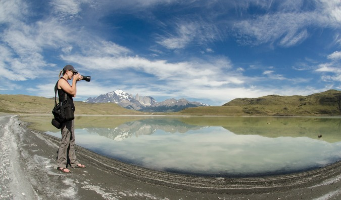 A woman standing in nature taking photos with a professional camera