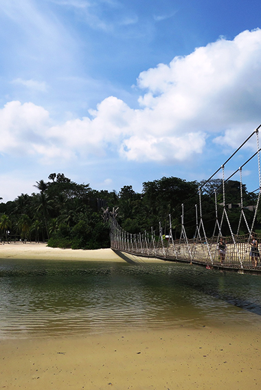 a hanging bridge over a beach on Sentosa island