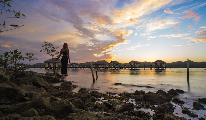A solo female traveler in front of incredible sunrise near water bungalows in Asia