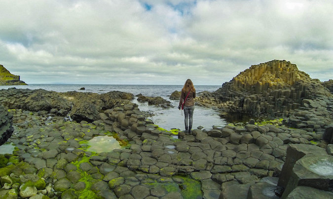 Solo girl traveler looking at beautiful rocky Icelandic landscape