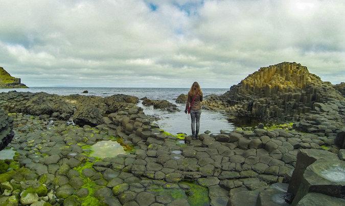 Solo female traveler looking at beautiful rocky Icelandic landscape near the ocean