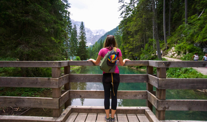 Solo female traveler looking over a picturesque forest landscape near a river