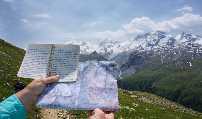 Travel journal in front of an amazing snow capped mountain range abroad