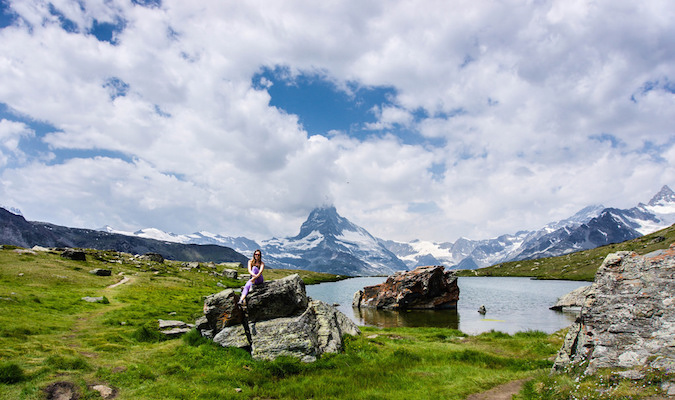 Solo female traveler sitting on a rock in a beautiful landscape overseas