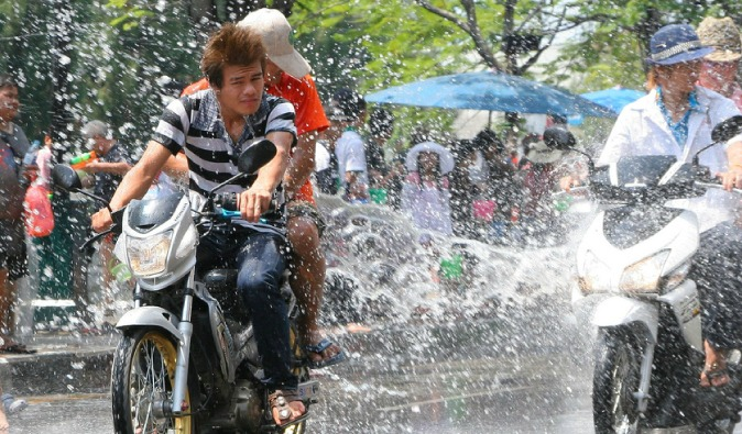 Motorcyclists getting splashed on Songkran, Thailand's New Year
