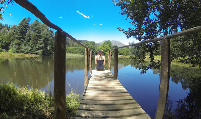 Solo Female Traveler relaxing by a South African lake on a nice day