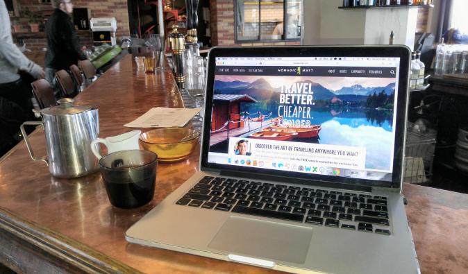 Photo of nomadicmatt.com open on a laptop in a hostel in Iceland