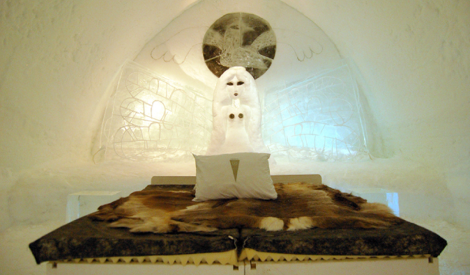 Big bed in the Swedish Ice Hotel with animal fur blankets and ice sculptures