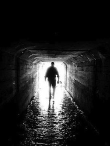 Man walking through a dark tunnel to get to the end