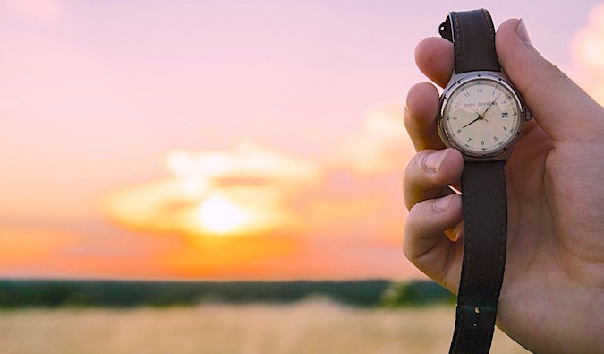 a man holding an old watch at sunset