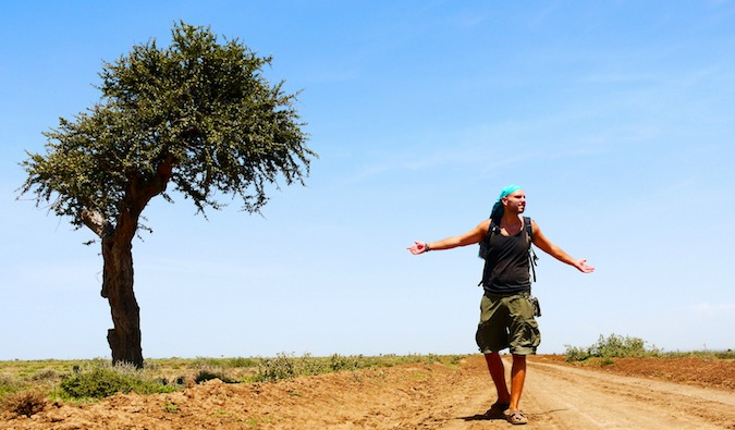 Tomislav, travel blogger stands next to a lone tree in Tanzania Africa