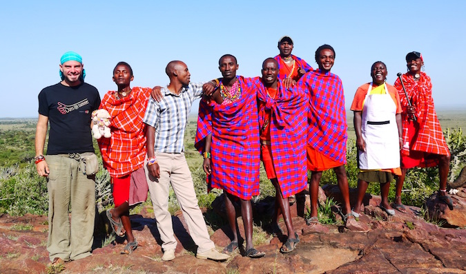 A traveler posing with the Massai people in Kenya