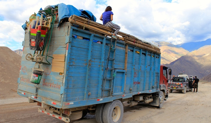 A backpacker hitchhiking on top of a truck in Peru