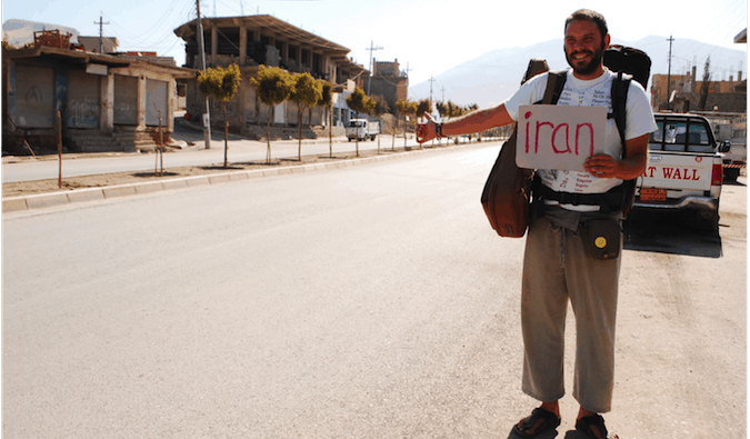 A solo backpacker hitchhiking in Iraq while holding a sign