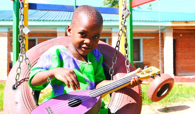 A young African child dressed in colorful clothing playing a small guitar
