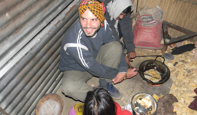 A solo traveler cooking with host family in a small hut overseas