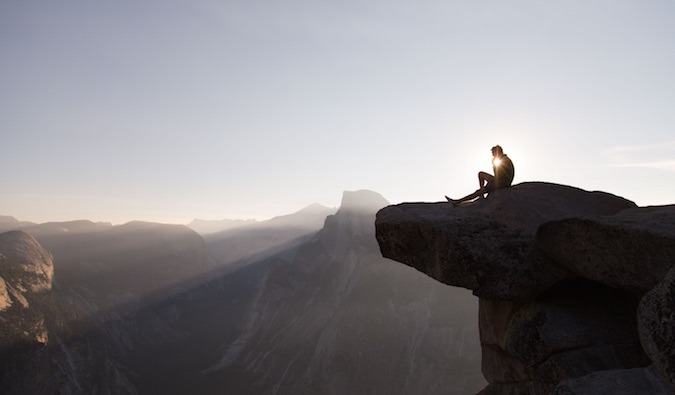 man sitting on a mountain while traveling