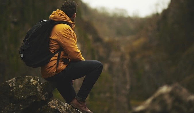 A solo hiker in a yellow jacket sitting in the mountains looking at the scenery around him
