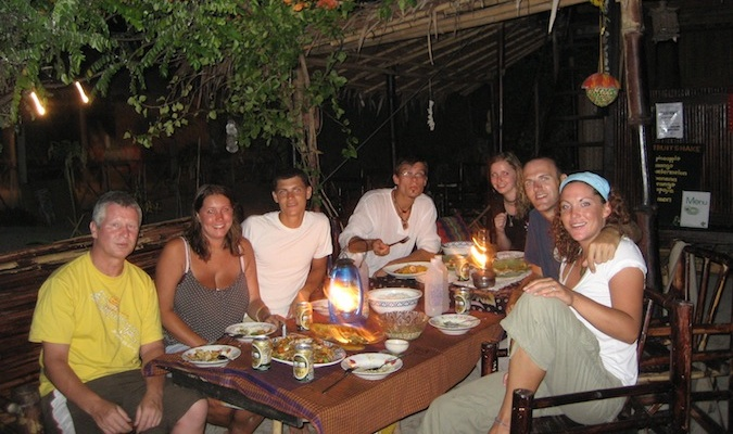 Traveling friends eating together at a hostel in Thailand