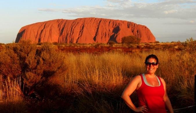 A solo female traveler posing near Uluru in Australia