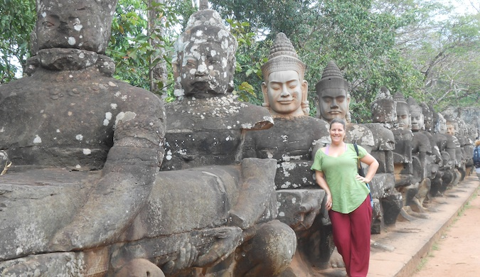A solo female traveler posing near religious statues while tarveling the world