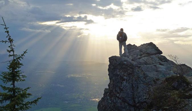 Hombre que viaja de pie en una montaña después de ir de excursión