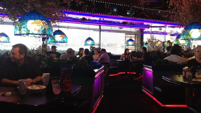 People eating a lot of good cheap food in a dim restaurant Las Vegas decorated with neon lights