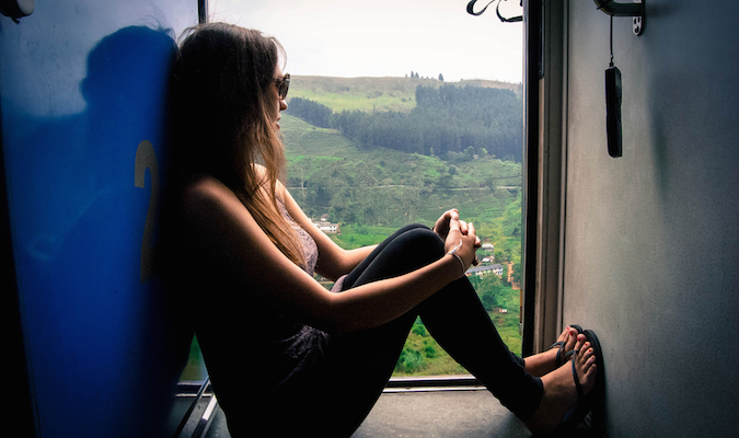 a solo traveler looking across the landscape from a train